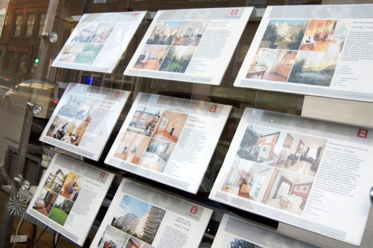 Signs show property details lined up in a grid in the window of a real estate agency.
