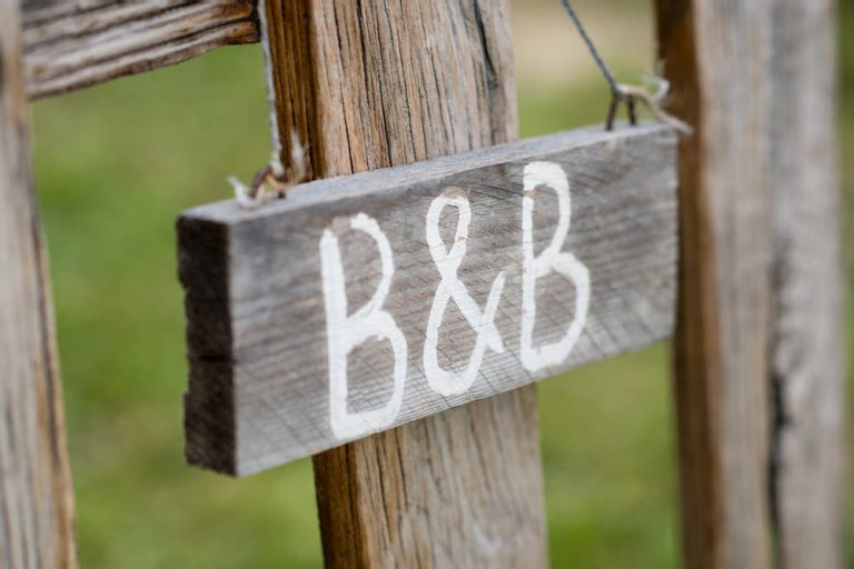 Wooden B&B sign hanging from a fence on a piece of string.