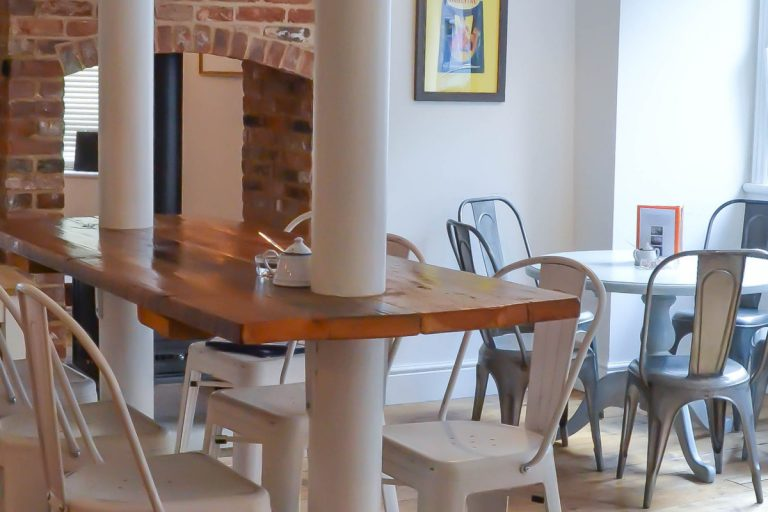 Tables and chairs in Bang In Wells, a modern, minimalist café and bar in the heart of Wells-next-the-Sea.