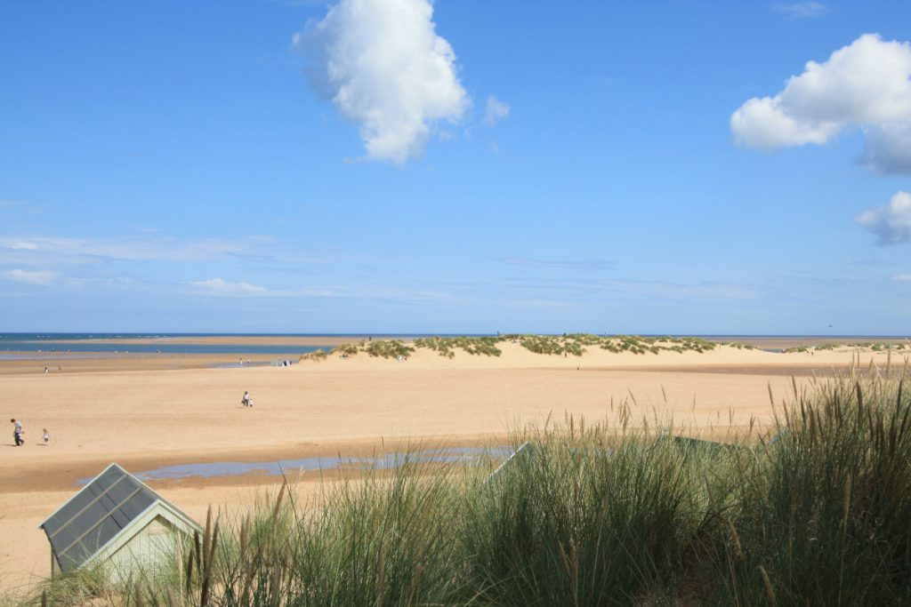 Wells-next-the-Sea beach at low tide overlooking grassy dunes and beach huts below, with a raised dune in the middle distance and some parents and children walking on the sand.