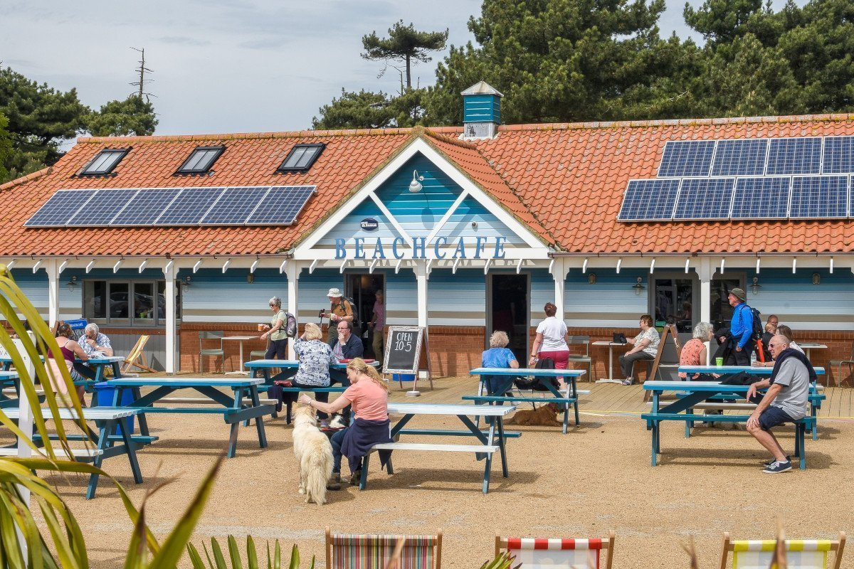 Outside the Beach Café situated next to the pinewoods, with customers sitting on outdoor seating.