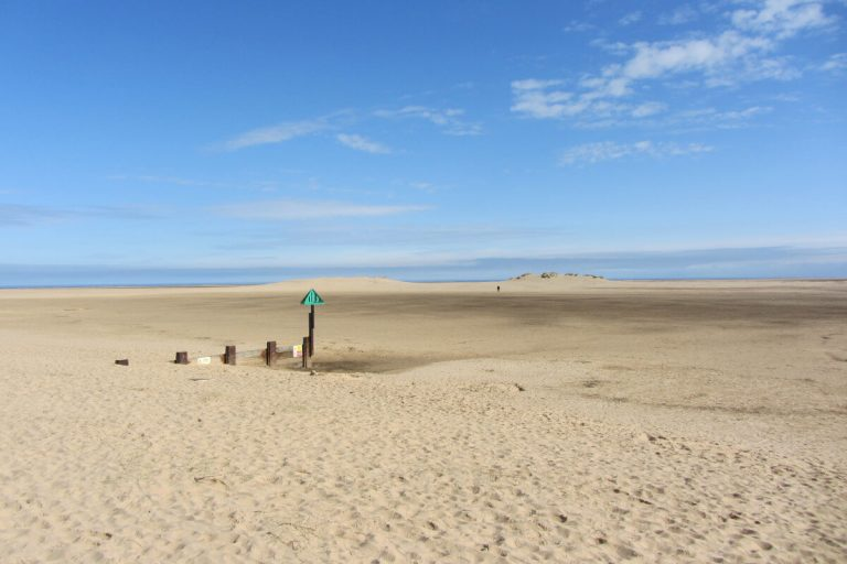 A groyne buried in the sand on Wells beach at low tide, a wide expanse of empty beach with a single figure walking in the distance.