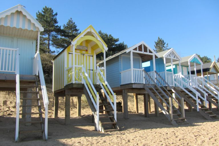 A row of pastel coloured beach huts on stilts in the sand at Wells beach, backed by pine trees.