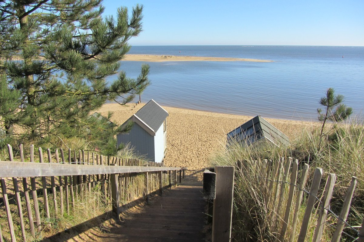Raised view from the steps at Wells beach that lead into the pinewoods, looking over the beach huts and out to sea.