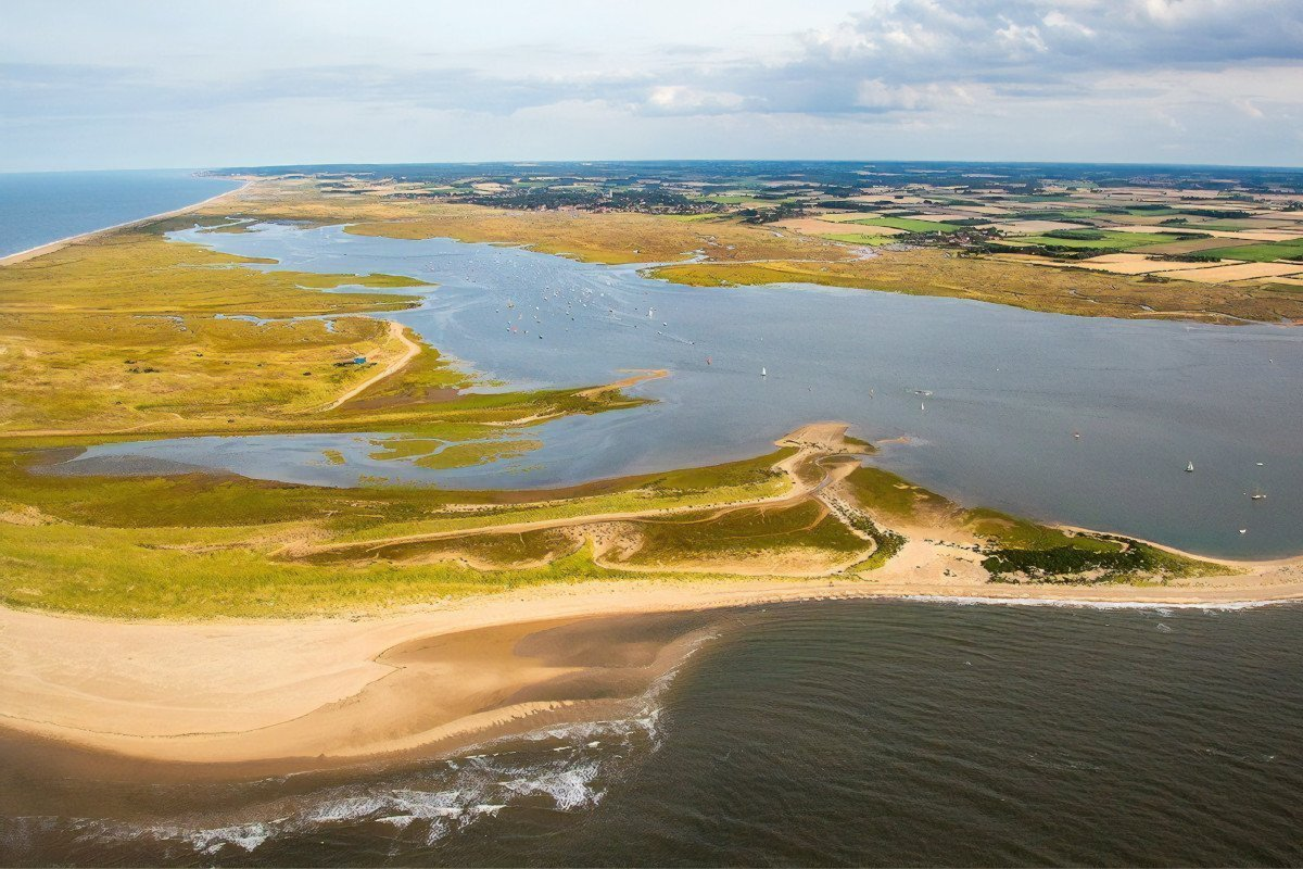An aerial view of Blakeney National Nature Reserve with sandy beach, saltmarsh and twisting muddy creeks flooded by the tide.