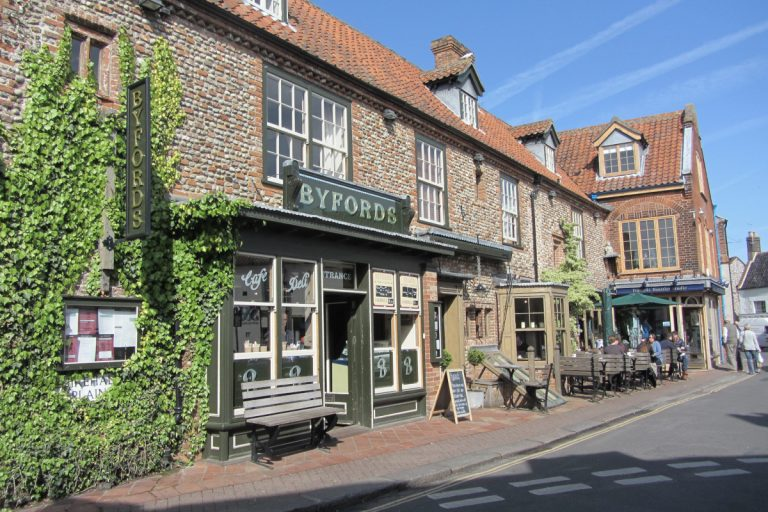 Exterior view of Byfords, a charming red-brick, ivy clad building with outdoor tables and benches.