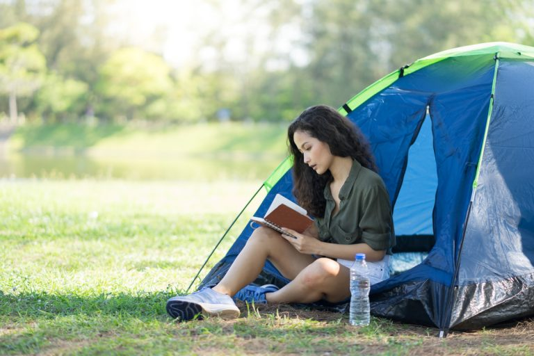 A girl sits reading a notebook in the entrance to a small blue tent.