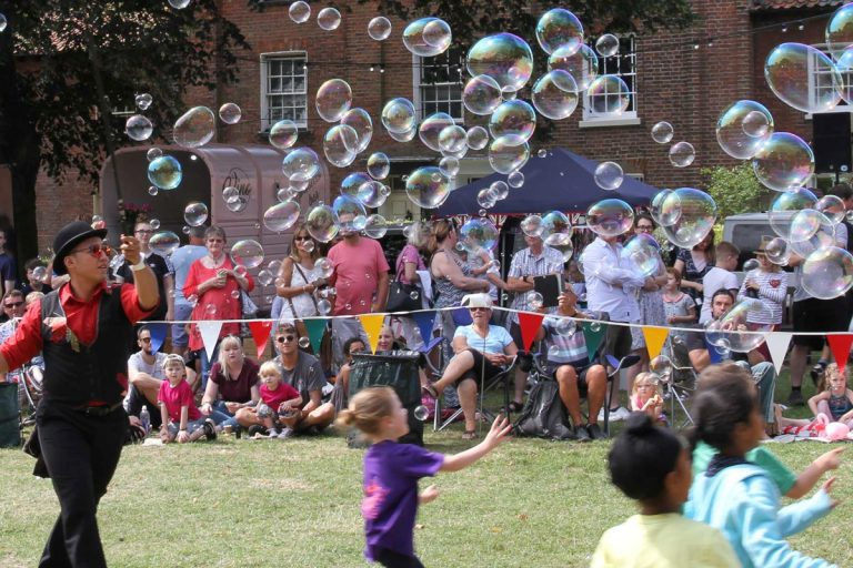 A man entertains children with giant soap bubbles at Wells Carnival while spectators watch from the sidelines.