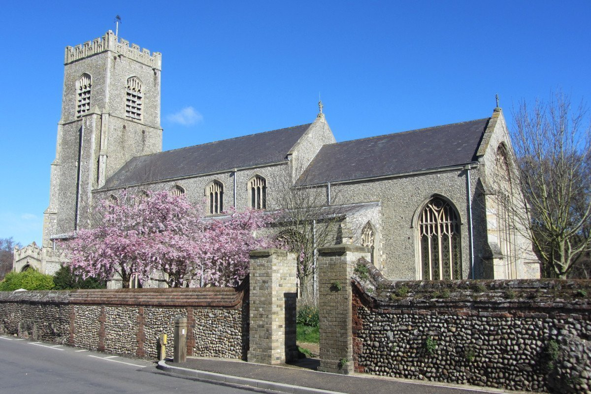 The handsome St Nicholas Church in Wells-next-the-Sea, separated from the road by a brick and flint wall with blossom trees in the grounds.