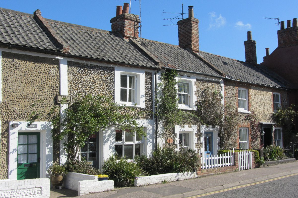 A row of traditional brick flint Norfolk cottages with picket fences and wisteria on a street in Wells-next-the-Sea.