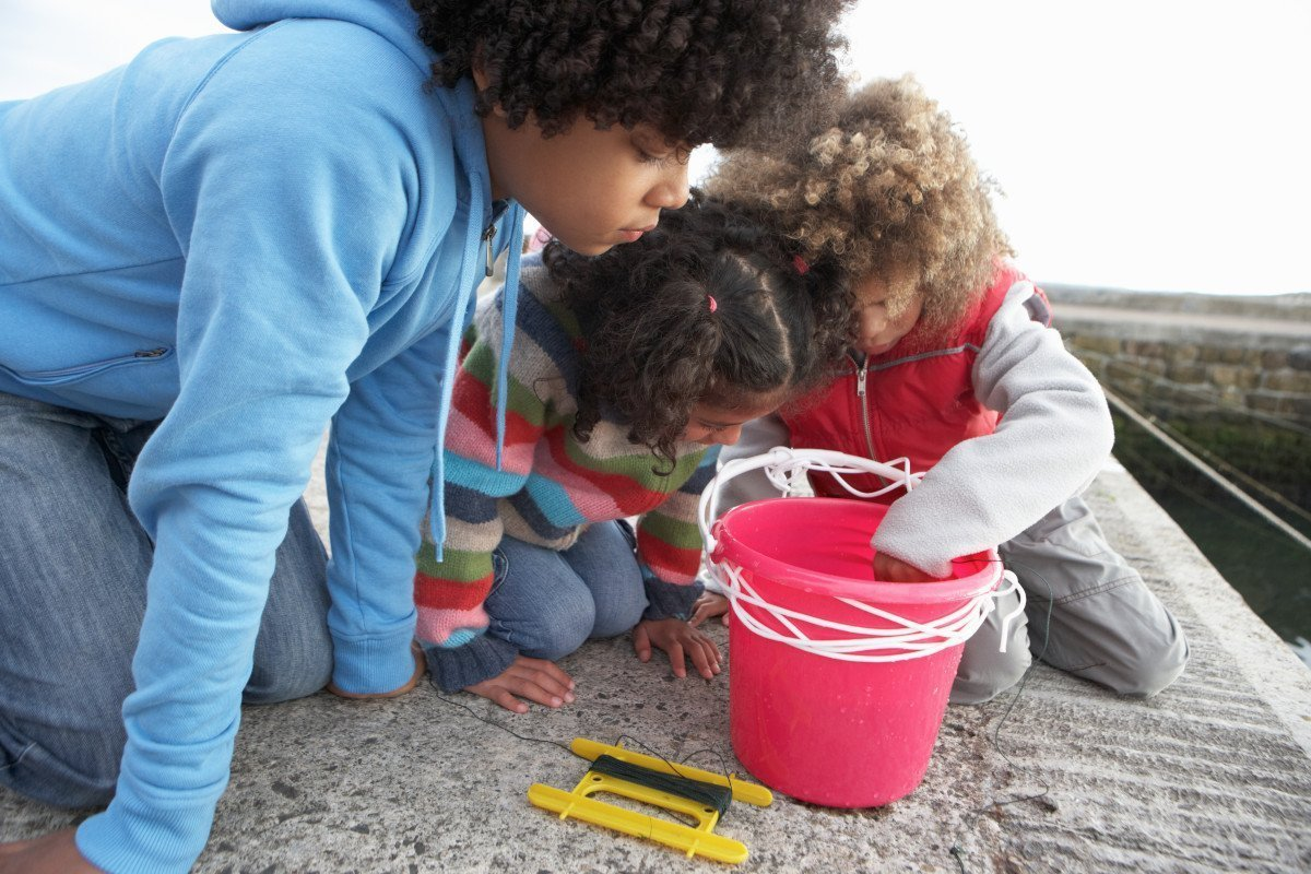 Three children looking into a pink bucket at the crabs they have caught fishing from the quay at Wells-next-the-Sea.