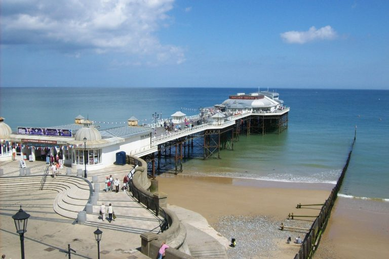 People strolling along Cromer Pier, a traditional Victorian seaside pier stretching out over the sea.
