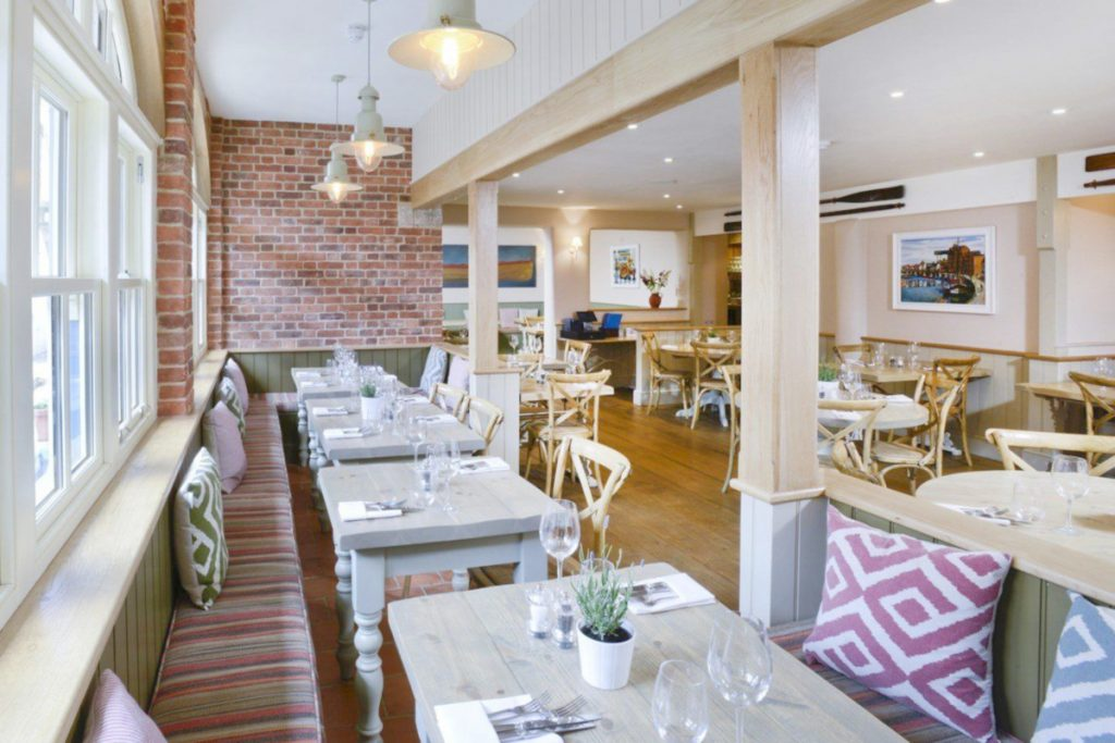 The restaurant at The Globe Inn in Wells-next-the-Sea with tables set and ready for diners.