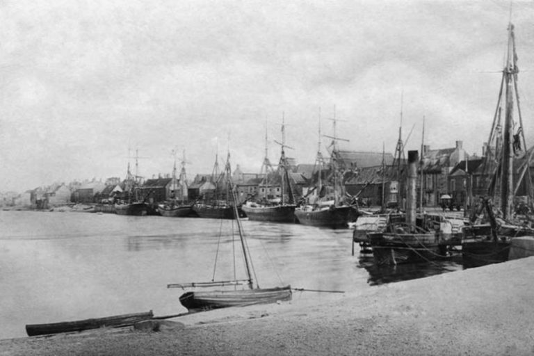 An old black and white photo of several boats and large ships in the harbour at Wells-next-the-Sea.