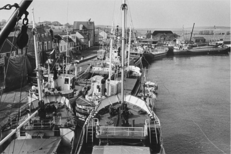 An old black and white photo of several large cargo vessels moored alongside the Quay at Wells-next-the-Sea.