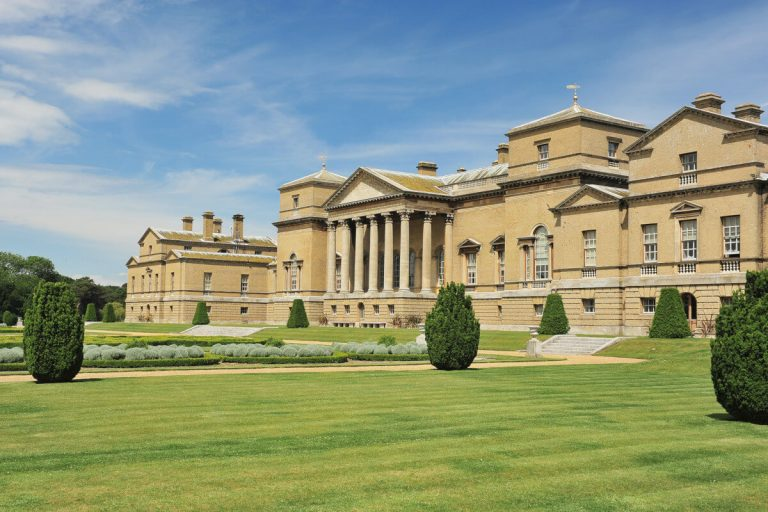 The exterior south facade and grounds of Holkham Hall, an 18th century stately home open to the public.