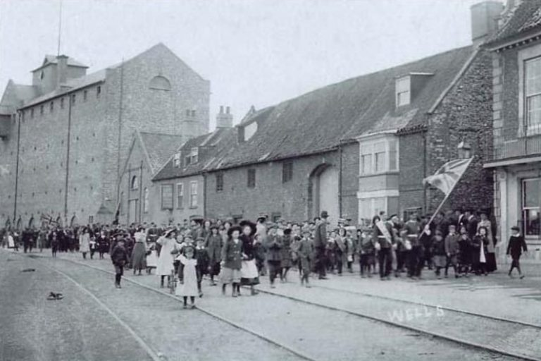 An old black and white photo of men, women and children marching in a parade on The Quay at Wells-next-the-Sea.