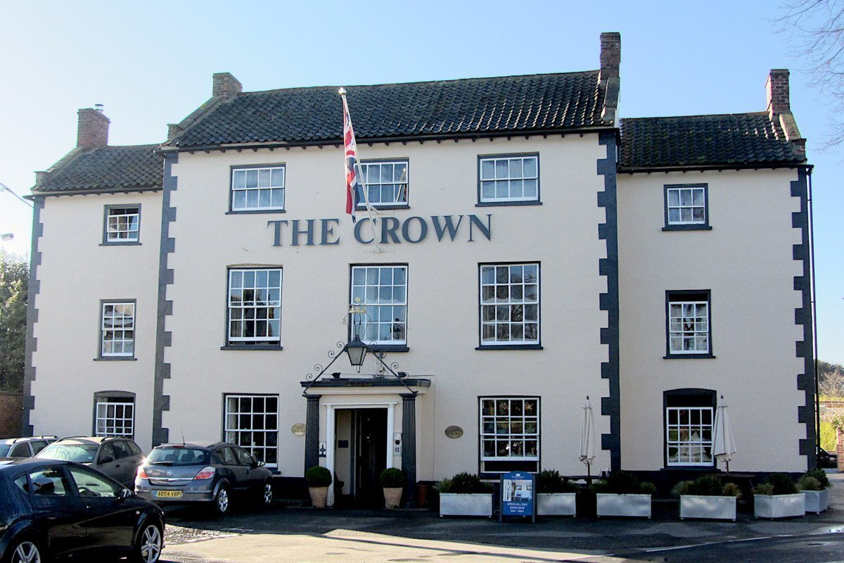 The handsome exterior of The Crown Hotel in Wells-next-the-Sea, displaying the Union Jack flag.