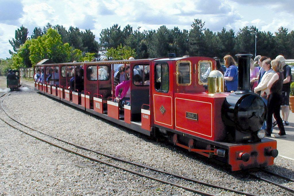 Miniature red steam train picks up passengers at Pinewoods Station.