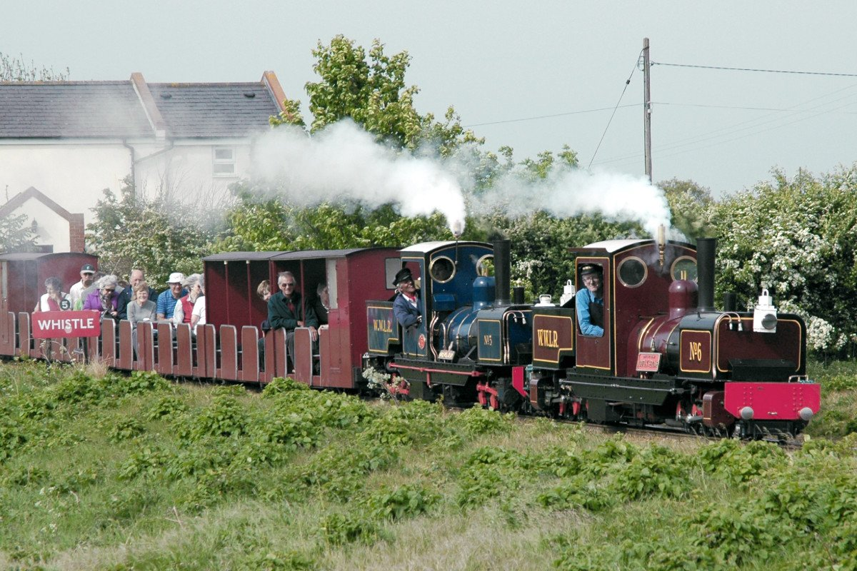 Two narrow gauge steam trains carrying passengers through the Norfolk countryside blowing their whistles.
