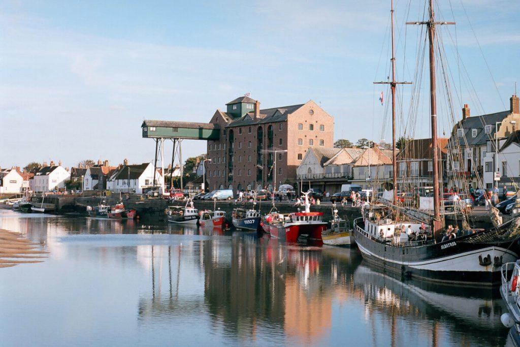 Wells-next-the-Sea Harbour & Quay with fishing boats, sailing barge & warehouse gantry.
