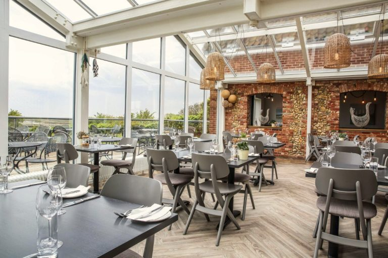 Inside the smart conservatory restaurant at The White Horse with exposed brick and flint walls and an outdoor terrace.