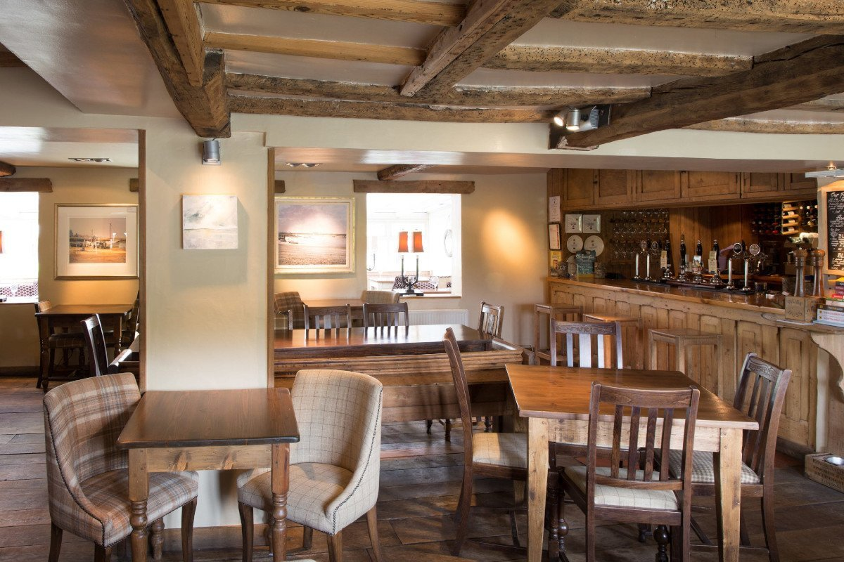 The bar and restaurant at The Wiveton Bell, with wooden beamed celings and tweed covered chairs, an inviting interior.