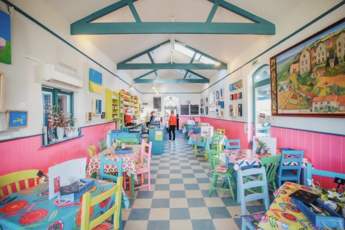 Wiveton Hall Café has a bright, cheery interior with checkerboard floor, multi-coloured tables and chairs, and floral patterned tablecloths.