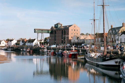 Wells Quay at low tide with fishing boats, a sailing barge and the famous overhanging warehouse gantry.