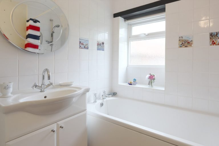 The bathroom at Antwis holiday cottage with porthole mirror.