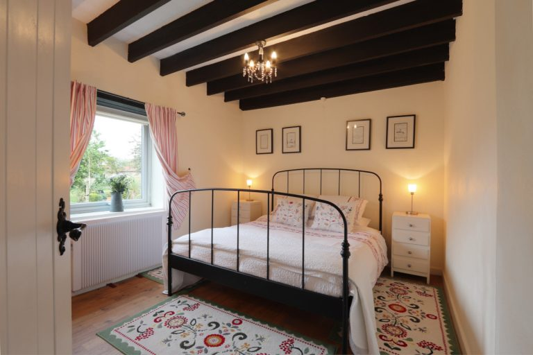 A double bedroom with oak beams in Antwis Cottage, Binham.