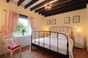 A double bedroom in Antwis Cottage with oak beamed ceiling.