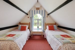 A bedroom with twin beds at Antwis Cottage, Binham.