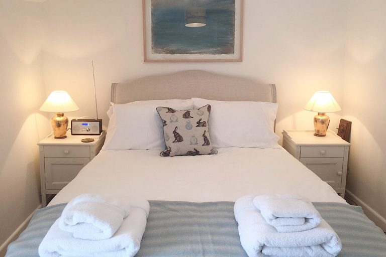 Double bed with towels at Carpenters Cottage in Wighton.