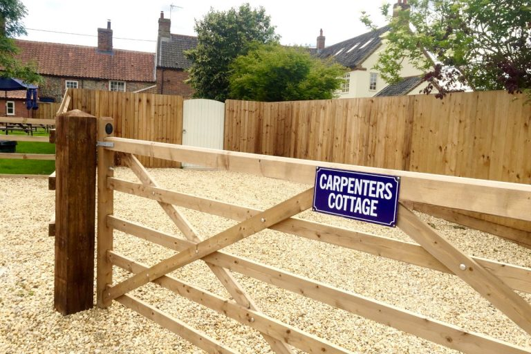 A wooden gated car park at Carpenters Cottage in Wighton.