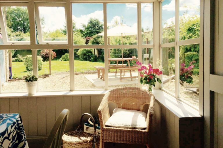 The sunny conservatory and garden at Grey Seal Cottage.
