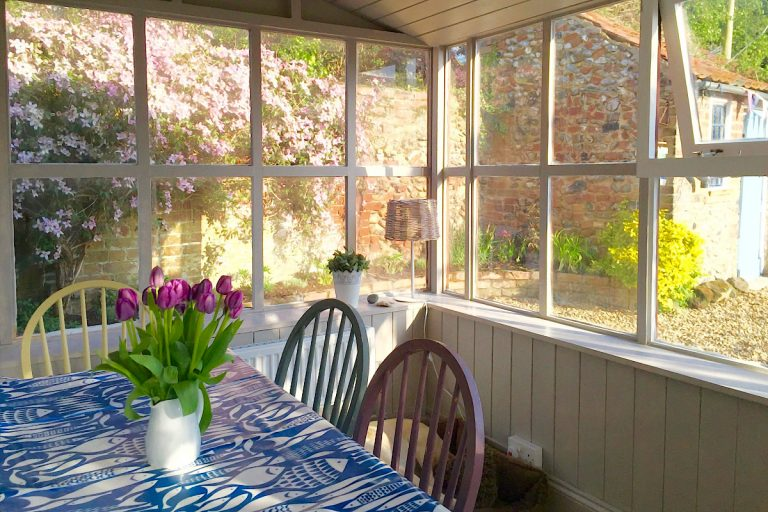 The conservatory dining room at Grey Seal Cottage.