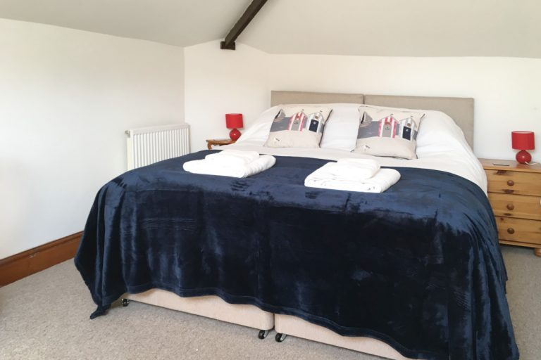 A double bed with folded towels at Hayloft Cottage, Wells-next-the-Sea