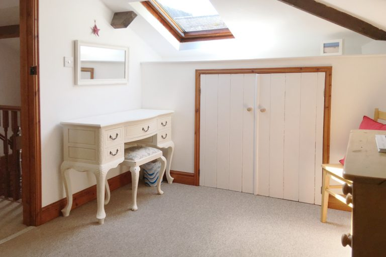 A dressing table and stool in a bedroom at Hayloft Cottage in Wells, Norfolk