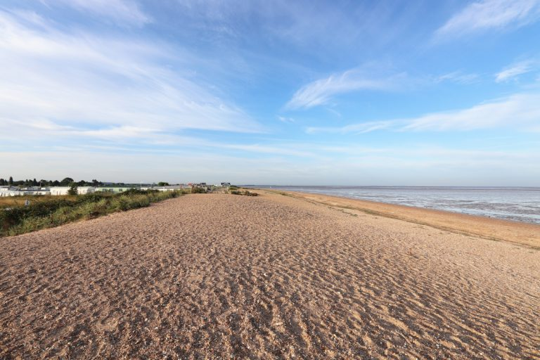 An empty Snettisham beach under a big blue sky with distant buildings and caravans.