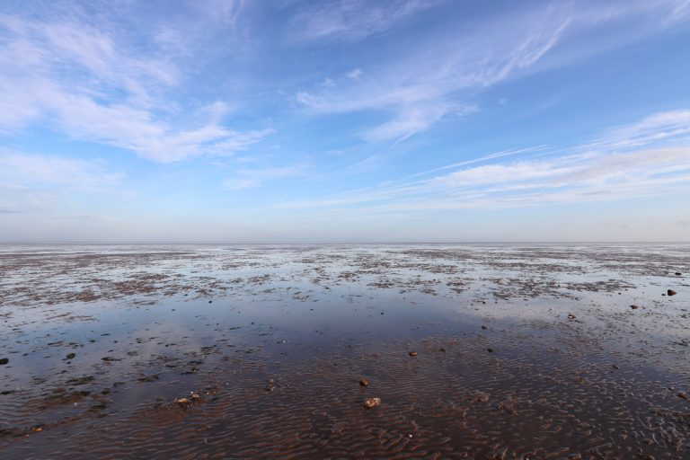 An empty Snettisham beach at low tide with the blue sky reflected in mudflats.