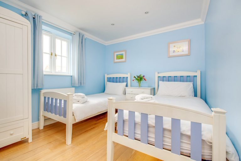 A pale blue twin bedroom at Tolly House in Wells.
