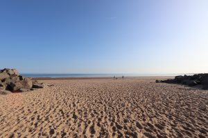 Sandy beach and dog walkers at Brancaster in Norfolk.
