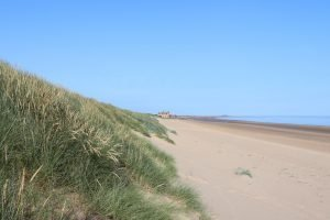 Grassy dunes and distant clubhouse at Brancaster beach.