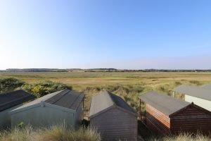 Beach huts overlooking fields at Brancaster.