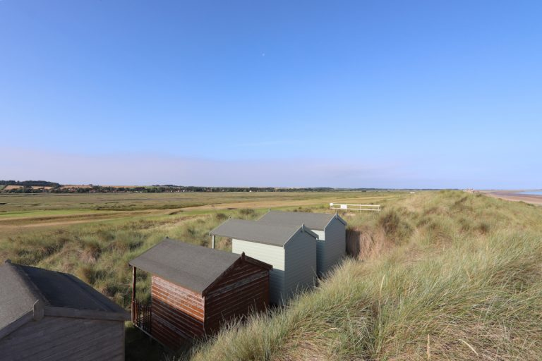 Beach huts nestled in the dunes at Brancaster beach.