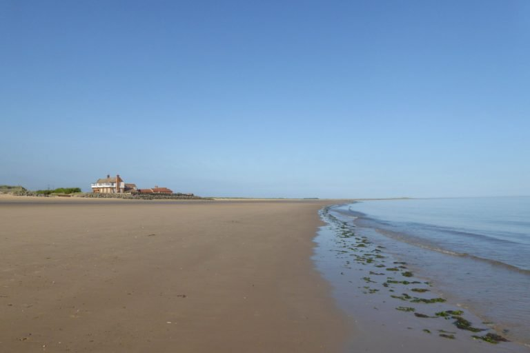 Empty beach and golf clubhouse at Brancaster.