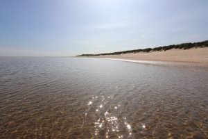 Sand dunes and crystal clear water at Burnham Overy Staithe beach.