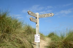 A wooden signpost on the beach at Burnham Overy Staithe.