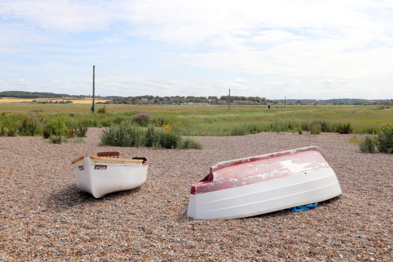 Two boats, one upturned, on Cley beach in Norfolk.